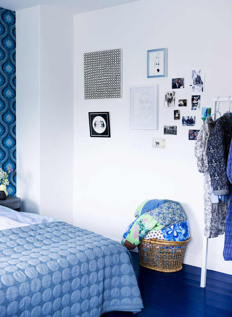 a blue bedroom makeover with frames on the wall