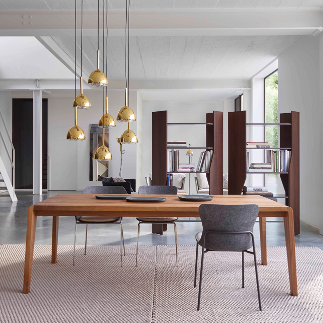 A cluster of pendants hung at various heights over a dining table is perfect for creating a focal point and a bit of drama brass bell pendant lights by