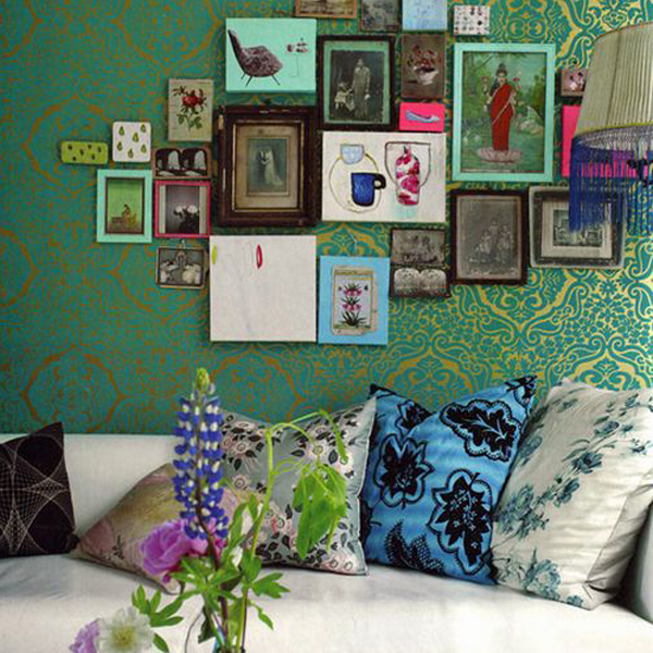 eclectic gallery wall against designers guild wallpaper