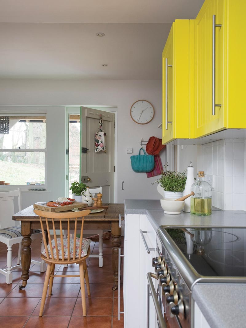 a kitchen with a pop of colour in the wall units